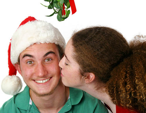 A teen girl kissing a very surprised boy under the mistletoe.